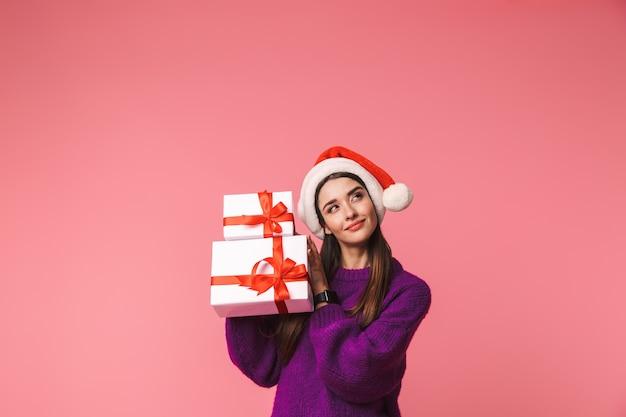 크리스마스 모자를 쓰고 선물 상자를 들고 핑크 이상 격리 포즈 아름 다운 젊은 생각 여자의 이미지. 프리미엄 사진