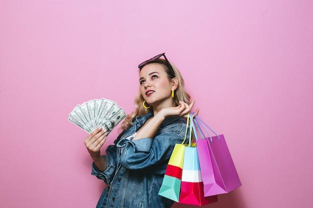 Изображение счастливой блондинки, думая о чем-то и держа банкноты и сумки на розовой стене Premium Фотографии
