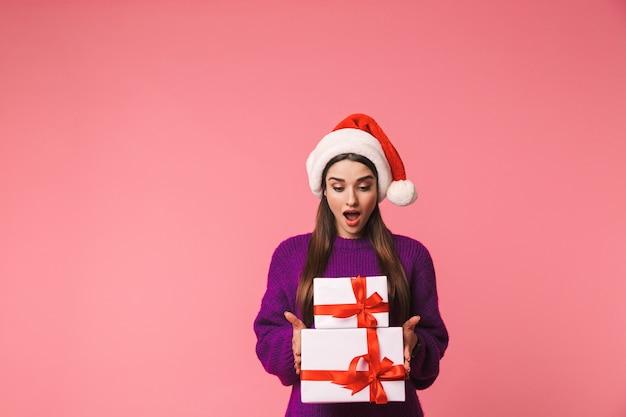 크리스마스 모자를 쓰고 선물 상자를 들고 핑크 이상 격리 포즈 충격 된 젊은 감정적 인 여자의 이미지. 프리미엄 사진