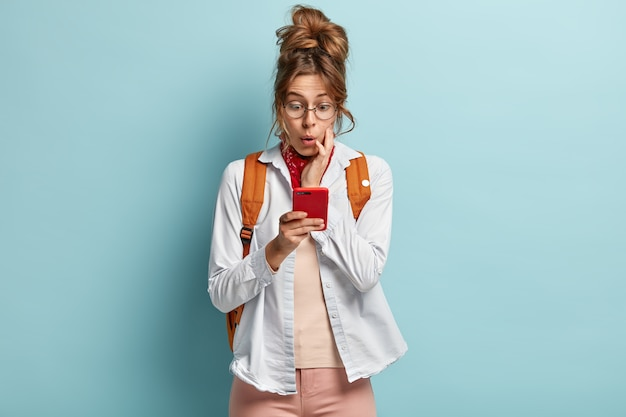 Изображение изумленной молодой женщины, пристрастившейся к интернету, сети через мобильный телефон, удивленной ограничениям, с темными зачесанными волосами Бесплатные Фотографии
