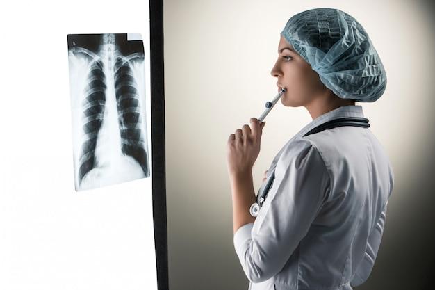 Изображение привлекательная женщина-врач, глядя на результаты рентгеновского Бесплатные Фотографии