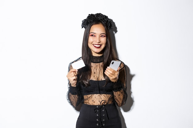ゴシックレースのドレスと黒い花輪で、クレジットカードで携帯電話を持って、喜んで笑顔で脇を見て、美しいアジアの女性の画像。 無料写真