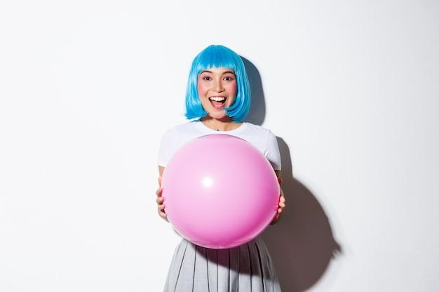 Изображение веселой азиатской девушки в синем парике, празднующей праздник, одетой в костюм для хэллоуина Бесплатные Фотографии
