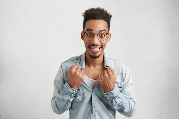 楕円形の顔を持つ陽気な男性のイメージは、丸い眼鏡をかけ、シャツを引き裂きます、 無料写真
