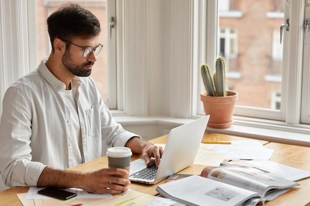 Изображение сосредоточенного небритого бизнесмена смотрит важный веб-семинар или онлайн-конференцию Бесплатные Фотографии