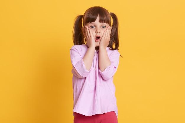 Изображение эмоционального испуганного удивленного ребенка кладя руки на щеки, раскрывая рот и глаза широко, представляя изолированный над желтой стеной. концепция детей и эмоций. Premium Фотографии