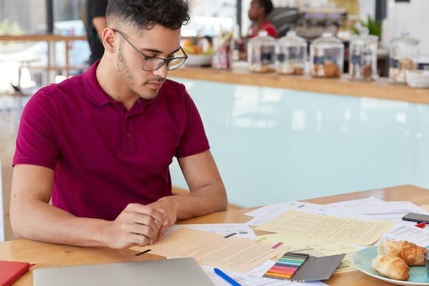 焦点を絞った男子学生の画像は、財務報告書を作成し、書類を注意深く見て、おいしいクロワッサンを食べ、昇進のための空きスペースがあるカフェのインテリアでポーズをとります。フリーランスの仕事 無料写真