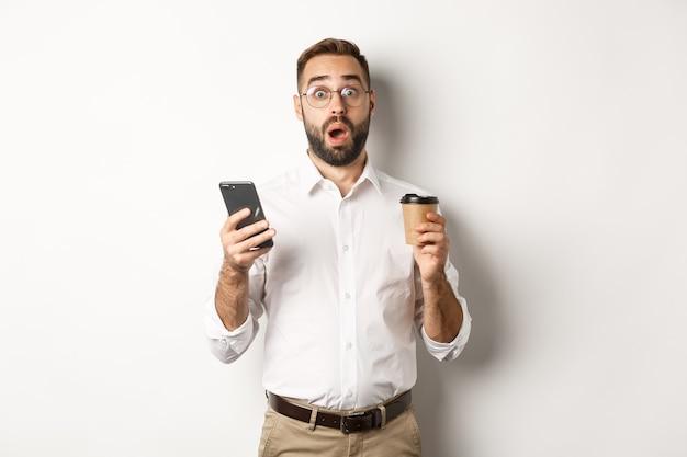 잘 생긴 관리 커피를 마시고, 휴대 전화의 메시지에 놀란 반응, 서있는 이미지 무료 사진