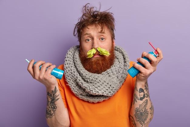 Образ больного рыжеволосого мужчины с насморком, носовым платком в ноздрях, носит вязаный теплый шарф на шее Бесплатные Фотографии