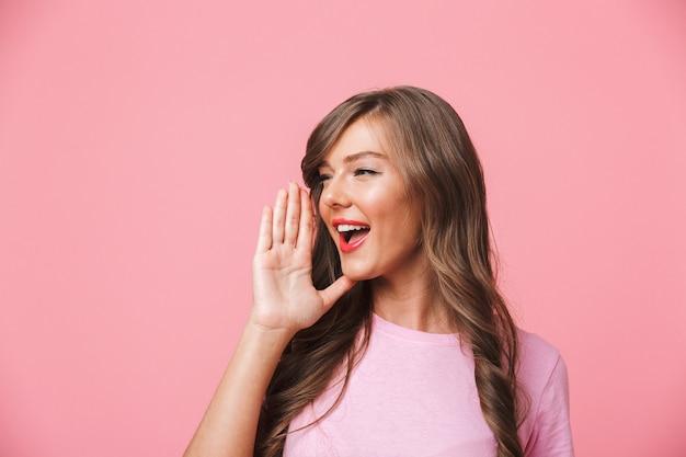 Copyspaceをよそ見と叫びまたはピンクの背景に分離された誰かを呼び出すと長い茶色の髪とうれしそうなヨーロッパの女性のイメージ Premium写真