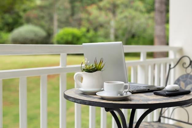Изображение ноутбука с чашкой кофе и растения на столе на балконе с видом на сад. Premium Фотографии