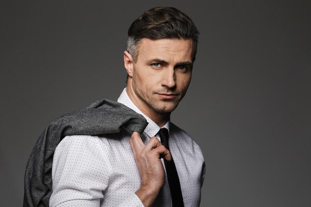 ビジネススーツを着て、灰色の壁に分離された彼の肩にジャケットを保持している成熟した剃っていない男のイメージ Premium写真