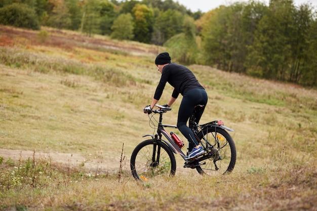 Изображение велосипедиста mauntain на лугу возле леса, вид сбоку спортивный мужской велосипед во время отпуска Premium Фотографии