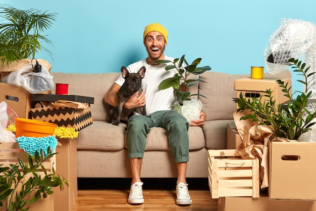 ポジティブなファッショナブルな男のイメージは、新しいアパートを借りて、お気に入りの犬と一緒に住んでいます 無料写真