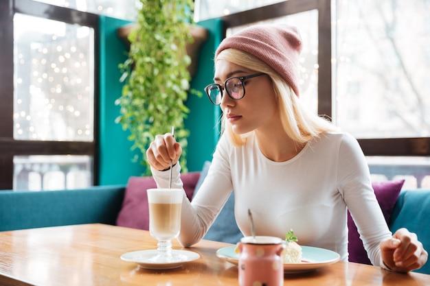 Изображение шляпы и стекел довольно молодой дамы нося есть торт и выпивая кофе пока сидящ в кафе. Бесплатные Фотографии