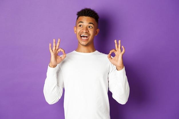 満足している男子生徒の画像。満足そうに見え、左上隅を見て、大丈夫な兆候を示し、紫色の上に立っています。 Premium写真