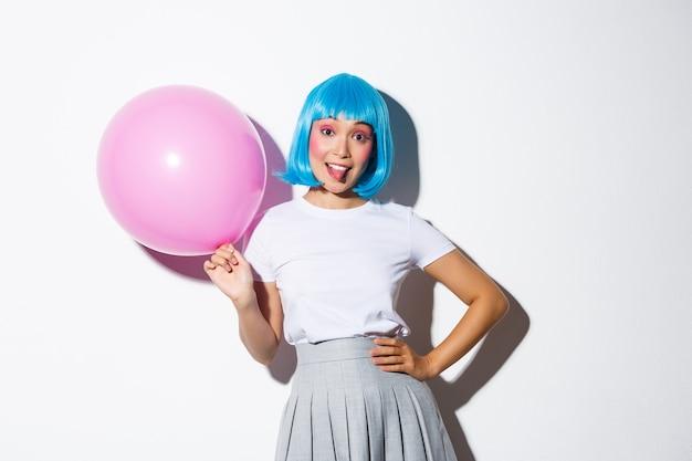 휴일을 축 하하고, 분홍색 풍선을 들고, 혀를 보여주는, Backgound 서 파란색 가발에 바보 같은 파티 소녀의 이미지. 무료 사진