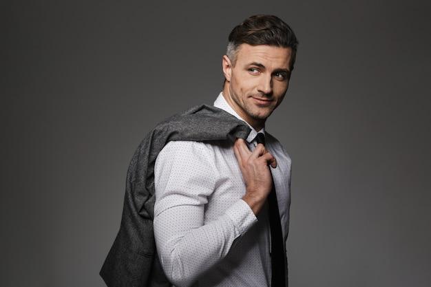 笑顔で衣装を着て、灰色の壁に分離された彼の肩にジャケットを保持している成功した実業家のイメージ Premium写真