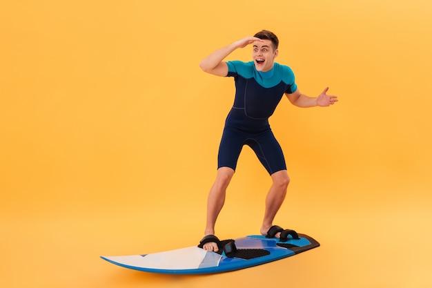 ウエットスーツでサーフィンボードを使用して波の上とよそ見で驚いた幸せなサーファーの画像 無料写真