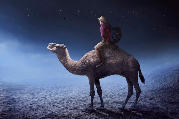 Изображение путешественника верхом на верблюде Premium Фотографии