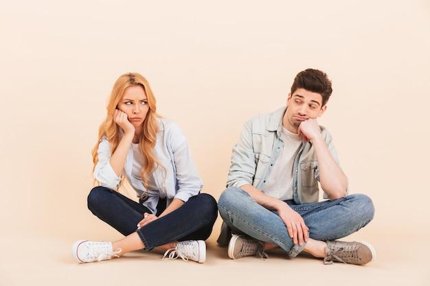 Изображение расстроенных мужчины и женщины, сидящих на полу в позе лотоса и подпирающих головы, надутых после драки или ссоры, изолированные на бежевой стене Premium Фотографии