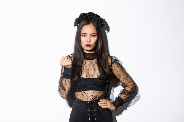 ハロウィーンの邪悪な魔女の衣装を着て、拳で誰かを脅かす女性の画像 無料写真