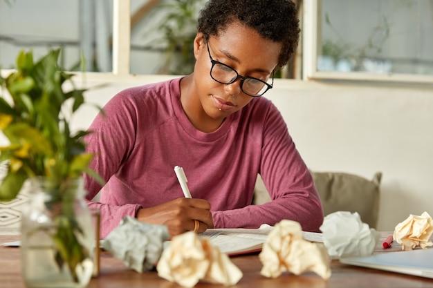 若い浅黒い肌の先生の画像は、大学で授業を行う準備をし、メモ帳でメモを取り、紙のボールで囲まれ、テーブルに創造的な混乱があり、焦点を合わせ、光学眼鏡をかけています 無料写真