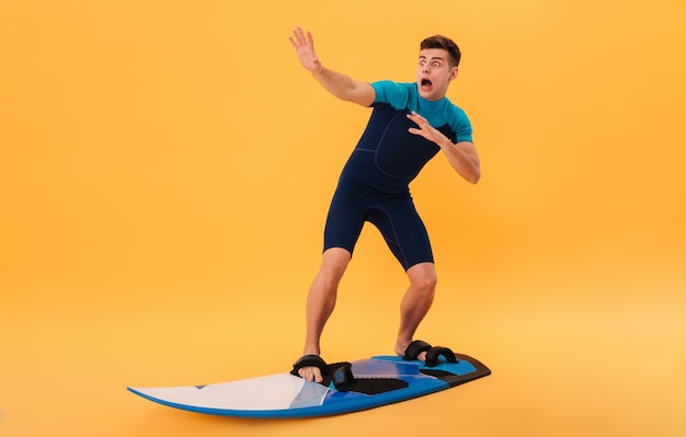 Image of scared screaming surfer in wetsuit using surfboard like on wave Free Photo