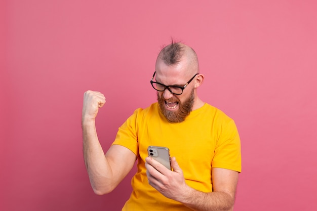 Immagine di urlando giovane barbuto uomo bello che celebra la vittoria e il successo molto eccitato sul rosa Foto Gratuite