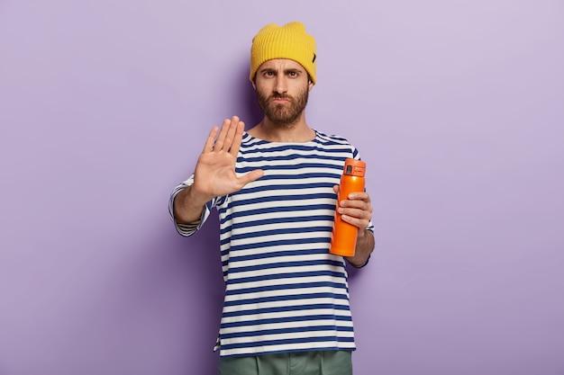 L'immagine del maschio serio dissacrato mostra il segno di rifiuto, fa il gesto di arresto con il palmo della mano che tiene il pallone da vuoto beve il tè al coperto, non ha desiderio di fare colazione. persone Foto Gratuite
