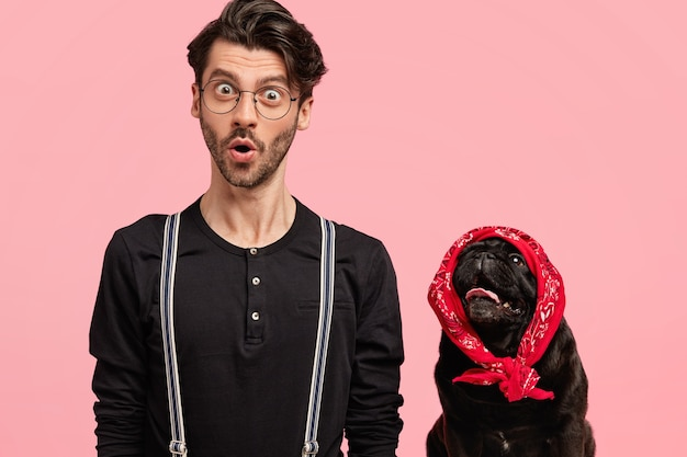 Immagine del giovane fotografo maschio stupefatto in vestiti alla moda, posa insieme al suo adorabile animale domestico, isolato sopra il muro rosa. il cane di razza nero indossa un'elegante bandana rossa sulla testa. Foto Gratuite