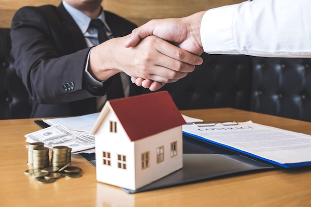 Image of successful deal of real estate, broker and client shaking hands after signing contract approved application form, concerning mortgage loan offer for and house insurance Premium Photo