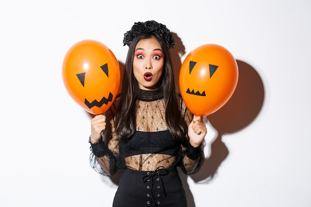 Image of surprised asian woman in witch costume celebrating halloween, holding balloons with scary faces Free Photo
