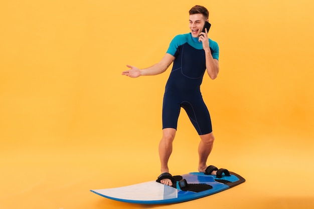 Image of surprised happy surfer in wetsuit using surfboard and talking by smartphone Free Photo