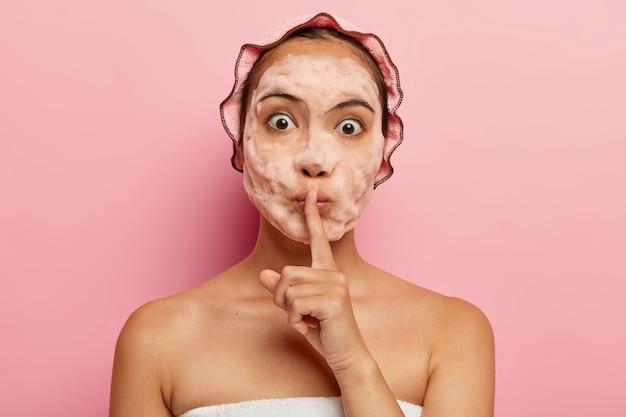 Immagine della signora coreana sorpresa con bolle di sapone sul viso, fa il gesto del silenzio, racconta il segreto di bellezza, pulisce ed esfolia la pelle, ha procedure cosmetiche durante il tempo libero, si prende cura di se stessa Foto Gratuite