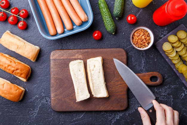 Image on top of table with ingredients for hot dogs, cutting board, man's hands Premium Photo
