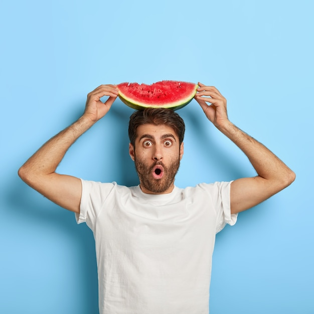 Immagine di un uomo con la barba lunga in una giornata estiva con in mano una fetta di anguria Foto Gratuite