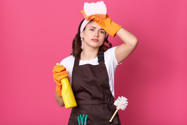 Image of upset tired housewife dresses brown apron with plunger and pins in pocket Premium Photo