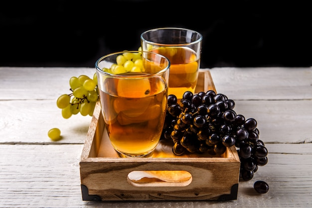 Image of wooden box with two glasses of wine, black and green grapes Premium Photo