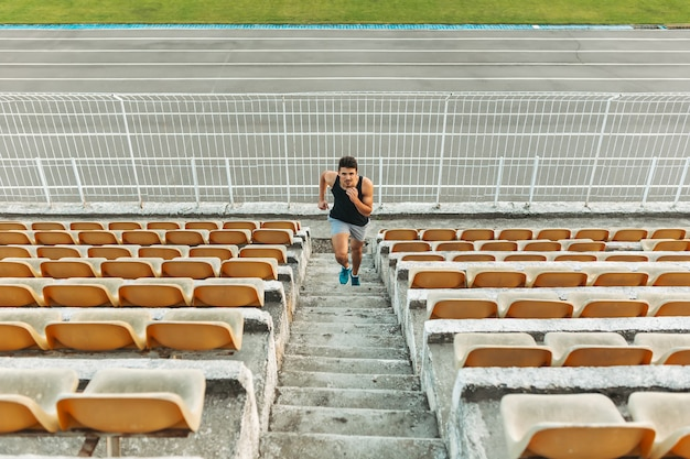 Image of young athletic man running by ladder at the stadium out Free Photo