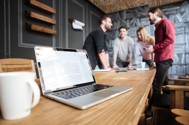 Immagine di giovani colleghi attraenti in piedi in ufficio e coworking Foto Gratuite