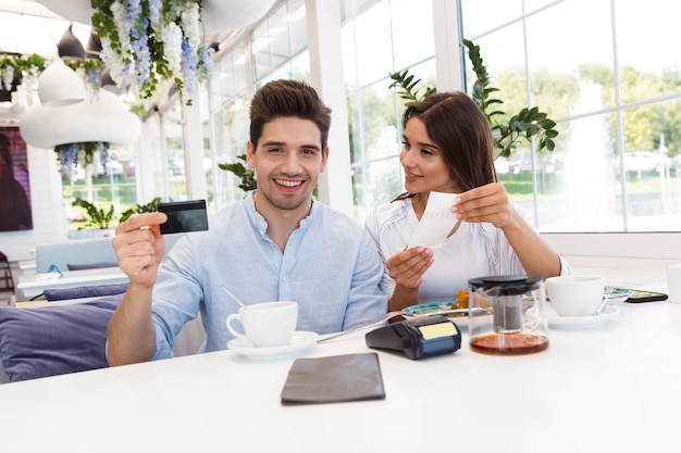 Image of a young happy loving couple sitting in cafe holding credit card and check. Premium Photo