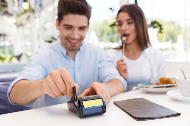 Image of a young happy loving couple sitting in cafe holding credit card and make payment. Premium Photo