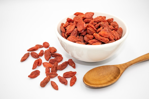 Images of dried goji berries in white cups and made into food on a white backgroundfractal background Premium Photo