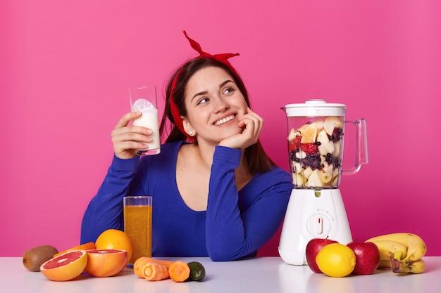 思いやりのある若い女性が青いシャツと赤いヘアバンドを手にミルクのガラスを着て、ピンクのスタジオでポーズをとるスムージーをする準備ができていると想像してください。健康的なライフスタイルとダイエットのコンセプトです。 Premium写真