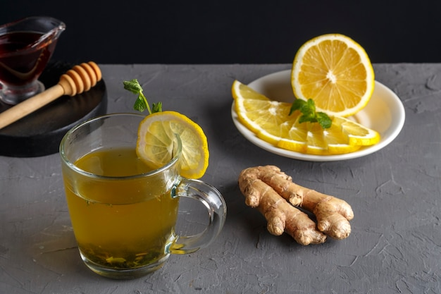 An immune ginger drink with honey and lemon in a glass cup next to the ingredients. horizontal photo Premium Photo