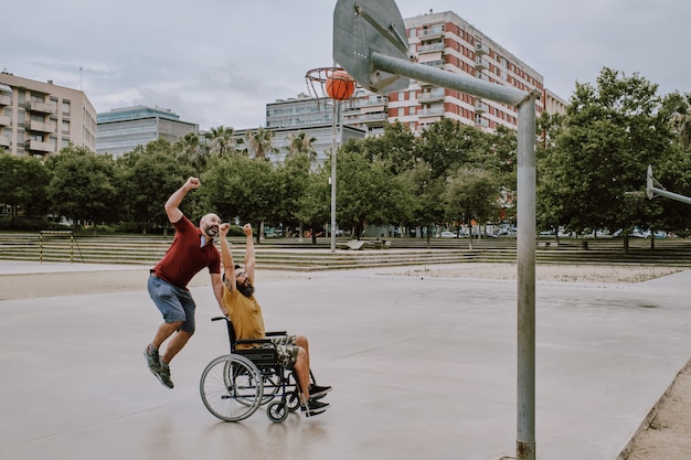 An impaired man in wheelchair plays basket with a friend Premium Photo