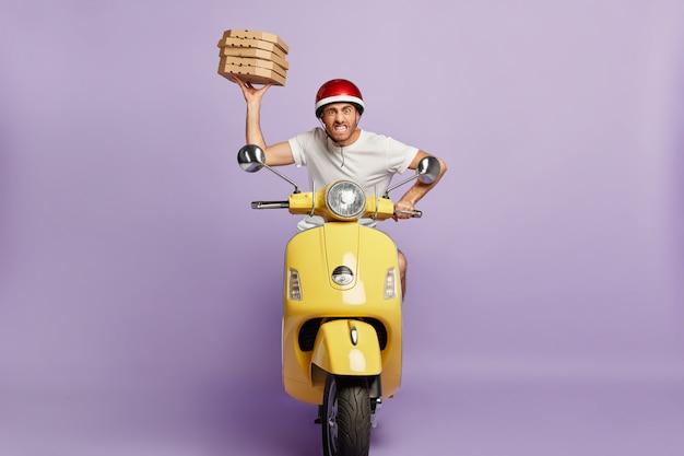 ピザの箱を持ってスクーターを運転するせっかちな配達員 無料写真