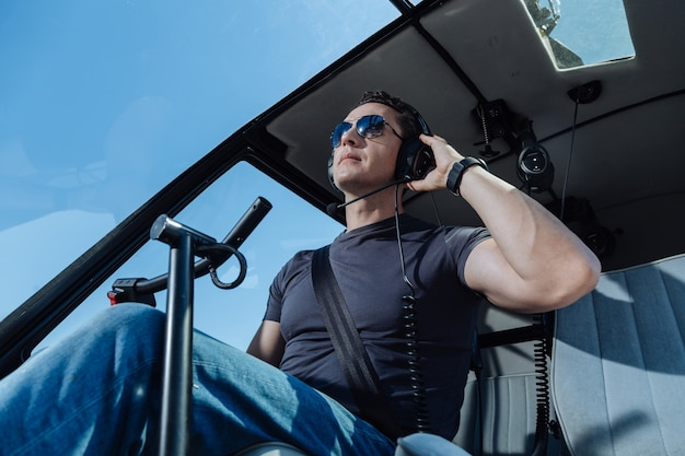 Important orders. serious young helicopter pilot using headphones and listening to the air traffic controller before starting the flight Premium Photo