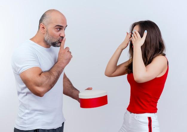 Под впечатлением от взрослых пара мужчина держит подарочную коробку в форме сердца, глядя на женщину и делает жест молчания, женщина держит руки возле глаз, стоя с закрытыми Бесплатные Фотографии